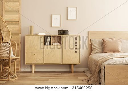 Two Small Graphics In Wooden Frames On Empty Wall Of Stylish Girl's Bedroom With Wooden Cabinet And