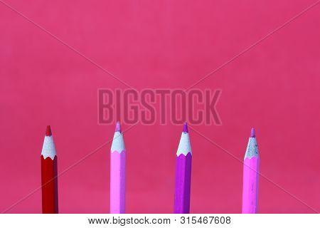 Colored Pencils In Coral And Pink. They Are Located Vertically. Against The Background Of Coral Colo