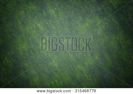 Construction Of Dark Green Background Light Spots Of Felt Fabric, Closeup. Texture Of Woolen Fleecy
