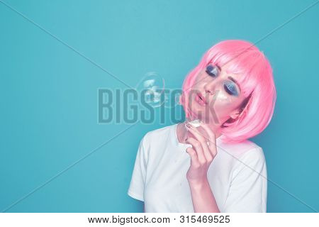 Young Woman Blowing Soap Bubbles. 90s Style Concept.