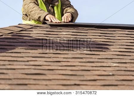 Building Under Construction Concept. Workman Installing Roof Asphalt Shingles Or Tiles Installed On