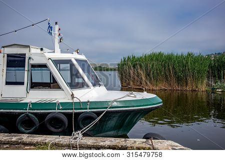 Street View With Tourist Boat Mooring, Ioannina Island On Lake Pamvotida Near The Beautiful Small Is