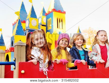 A Group Of Preschoolers Play And Smile On The Background Of A Childrens Amusement Park In The Form O