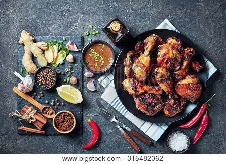 Spicy Grilled Caribbean Jerk Chicken Drumsticks And Thighs On A Black Platter On A Concrete Table Wi
