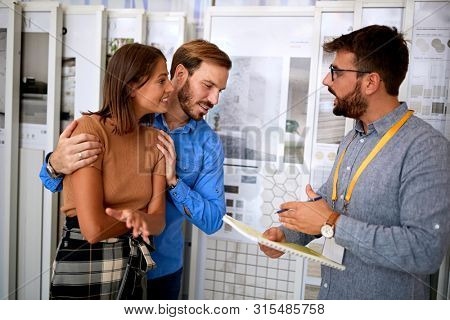 Young couple with salesman in store for the house