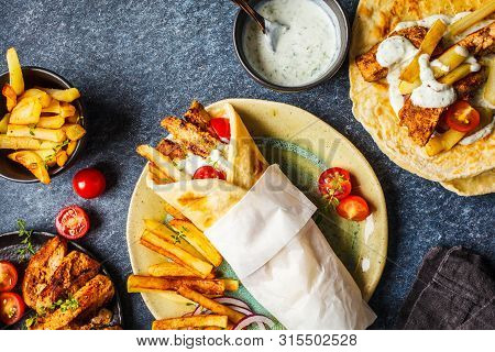 Gyros Souvlaki Wraps In Pita Bread With Chicken, Potatoes And Tzatziki Sauce, Blue Background, Top V
