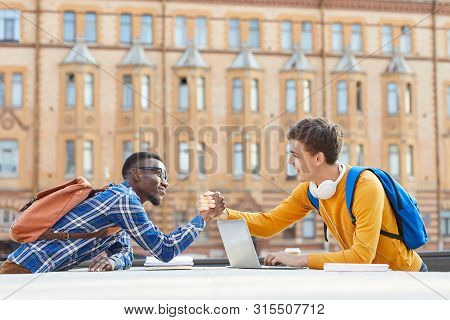 Side View Portrait Of Two Contemporary College Students, One Of Them African, Shaking Hands While St