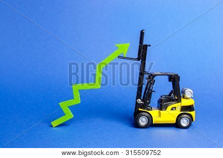 A Yellow Forklift Raises A Big Green Arrow Up. Growth In Production Rates And Development Of Industr