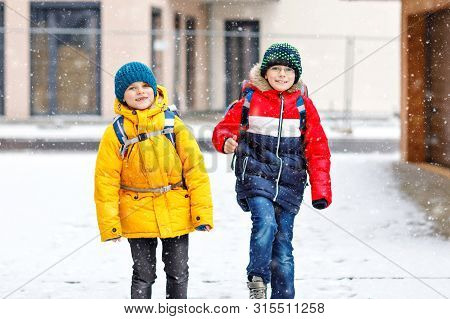 Two Little Kids Boys Of Elementary Class Walking To School During Snowfall. Happy Children Having Fu