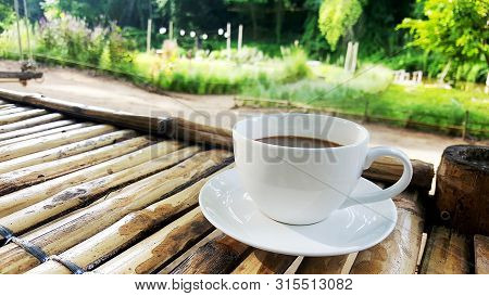 Hot Black Coffee In White Cup. A Cup Of Black Coffee On The Bamboo Wood Table In The Graden.