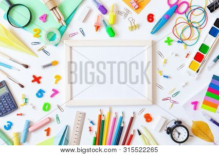 Empty Wooden Frame With Squared Paper, Alarm Clock, Different Stationery And Colorful Supplies On Wh