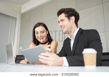 Young Business People Are Relaxing While Using Digital Tablet And Laptop Computer At The Office. Hap
