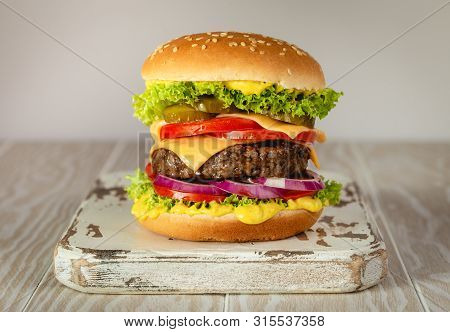 Delicious Burger With Meat, Melted Cheese, Dripping Sauce And Vegetables On White Rustic Background.