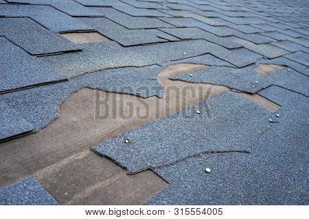 View Of Bitumen Shingles Roof Damage That Needs Repair.
