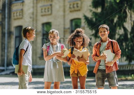 Four Adorable Multicultural Schoolchildren Standing In Schoolyard And Holding Books