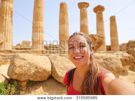 Happy Smiling Woman Taking Self Portrait With Greek Temple On The Background In The Valley Of The Te