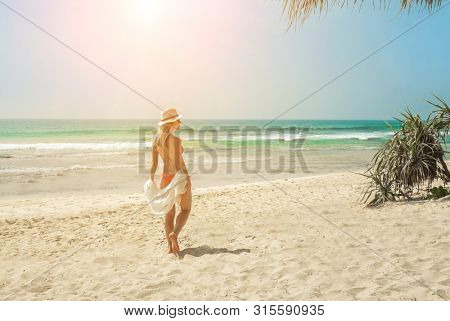 Happy traveller woman in white enjoys her tropical beach vacation in sunny day. Holidays, Travel, Coastline, Freedom concept.