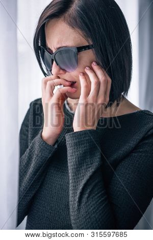Depressed Woman In Sunglasses Covering Mouth And Grieving At Home
