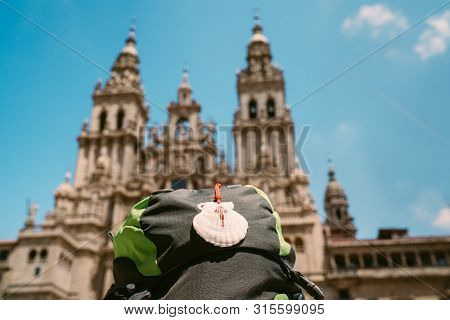 Pilgrim's Backpack With Famous Pilgrims' Mascot And Sign Seashell With Cross Of Saint James At  On T