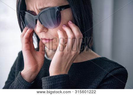 Depressed Lonely Woman In Sunglasses Grieving At Home