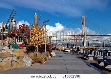 Promenade  Quay On The  Riverfront Of Fraser River  In New Westminster City And Three Bridges Over T
