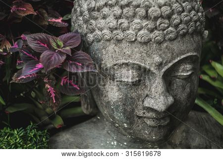 Stone Buddha Face Close-up. Handmade Carved Buddha Statue In Balinese Garden As Decoration.