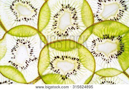 Top View Of Sliced Kiwi As Background. Fresh Cut Sliced Green Kiwifruit Kiwi Fruits On Brown Grey Bo