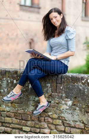 Smiling student outdoor reading a book