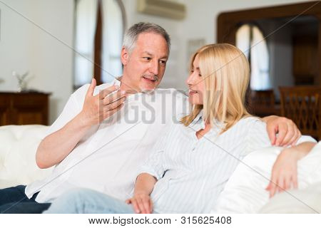 Portrait of an happy mature couple talking in their home. Shallow depth of field, focus on the man