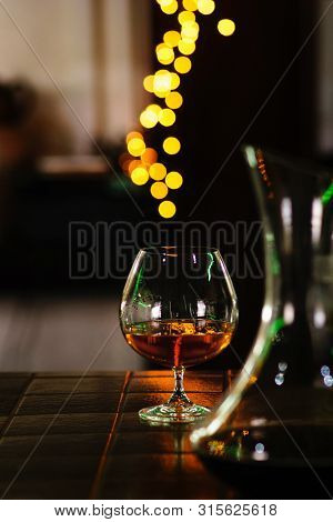 Snifter Of Brandy In Elegant Glass With Space For Text On Dark Colorful Background. Decanter Defocus