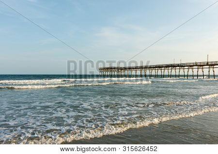 Fishing Pier Into The Atlantic Ocean, Sunset Beach, North Carolina; With Copy Space For Text, At Sun