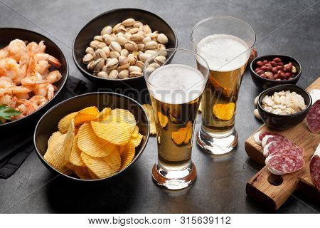 Draft beer and snacks on stone background. Nuts, chips, sausages and shrimps