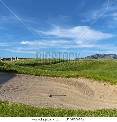 Square Golf course with sand bunker and vibrant fairway under blue sky on a sunny day poster