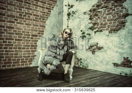 A full length portrait of a beautiful girl wearing a fur coat posing on the armchair. Beauty, winter fashion.