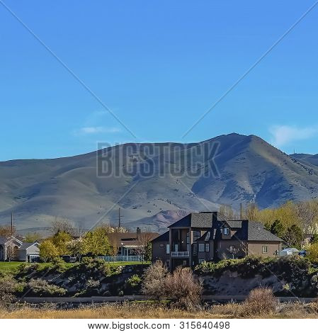Square Lakefront Houses With Towering Mountain And Blue Sky Background On A Sunny Day