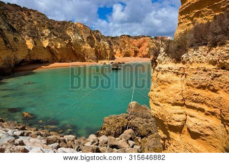 Praia da Dona Ana beach, Lagos, Algarve region, Portugal. Praia Dona Ana surrounded by steep colourful strata cliffs. One of the most picturesque beaches in Algarve.