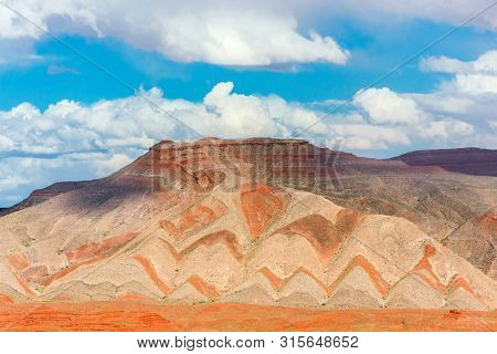 Interesting background of red banded strata viewed from Highway 163. The zigzag pattern is result of erosion of the tilted strata. Mexican Hat, Utah - USA.