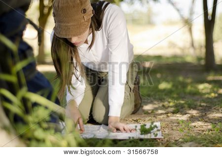 Young woman looking at a map on a hiking trip