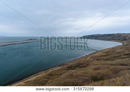 The Shore Of The Kerch Strait During The Construction Of The Kerch Bridge In Cloudy Weather With Clo