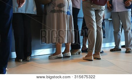 Close-up Of Women And Man Waiting In Queue In The Hospital Or Post. People Waiting Quietly For Their