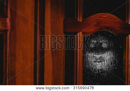 Creepy Evil Creature With Empty Eyes Looks Out The Window. Halloween Poster With Copy Space