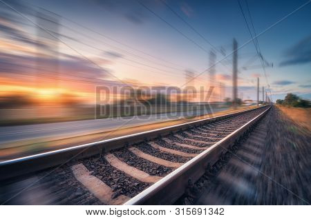 Railroad And Beautiful Blue Sky With Clouds At Sunset With Motion Blur Effect In Summer. Industrial