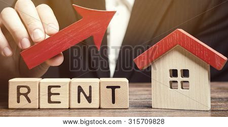 Wooden Blocks With The Word Rent, House And Up Arrow. The Concept Of The High Cost Of Rent For An Ap