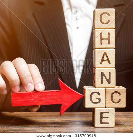 Businessman Points To Wooden Blocks With The Word Change To Chance. Personal Development. Career Gro