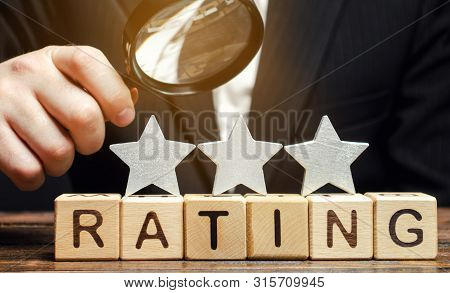 Wooden Blocks With The Word Rating, Three Stars And A Magnifying Glass In The Hands Of A Businessman