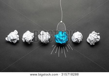 Light Bulb Sketch Drawing With Crumpled Blue Paper Ball On Blackboard. Successful Solution Of Proble