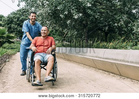 Disabled Man In Wheelchair Laughing During A Walk With His Nurse At Park, Concept Of Medical Care An