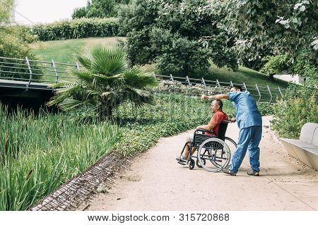 Disabled Man In A Wheelchair Talking With His Caretaker During A Walk, Concept Of Medical Care And R