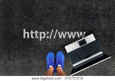 Website Address Or Url Concept. Man Legs In Shoes Standing On Asphalt Next To Laptop And Web Address
