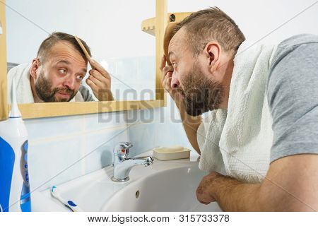 Adult Man Standing In Front Of The Bathroom Mirror Brushing His Short Hair Using Comb. Guy Investiga
